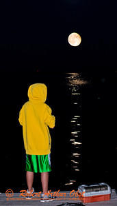 Gorgeous full 2012 Autumnal Equinox Harvest Moon rising over youth fisherman on Lake Mendota at the Lake Street Dock by Captain Bill's Waterfront near the outlet of Pheasant Branch Creek Conservany (USA WI Middleton; RAO 2012 Nikon D800 Image 6319-2)