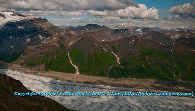 Glacier flowing off Regal Mountain and past colorful peaks north of Kennicott within Wrangell St. Elias National Park and Preserve (USA Alaska McCarthy)