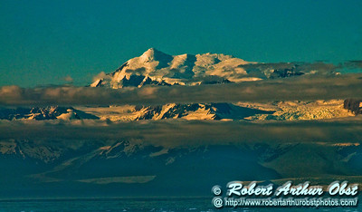 Mountains tower over Wrangell–St. Elias National Park and Preserve through eerie evening light between Glacier Bay and College Fjord within the Gulf of Alaska of the Pacific Ocean (USA Alaska Copper Center)