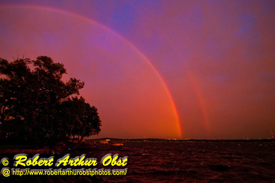 Unexpected dazzling iridescent double rainbow at sunset during a gusty rainstorm over Lake Mendota Park (USA WI Middleton)