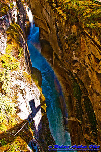 Rainbow between limestone cliffs over the churing falls of Maligne River Canyon within Jasper National Park (Canada Alberta Jasper)