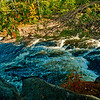 Autumn colors over Big Smokey Falls within Menominee Indian Nation on the wild Wolf River within northeastern Wisconsin near Keshena (USA WI Keshena)