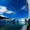 The Aialik Glacier flowing into Aialik Bay of the Pacific Ocean under blue skies from tour boat within Kenai Fjords National Park of the Kenai Peninsula (USA Alaska Seward)