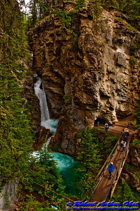Hikers observe Lower Falls and Emerald Pools of Johnston Creek in Johnston Canyon within Banff National Park (Canada Alberta Banff)