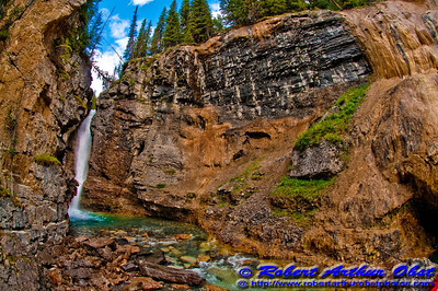 Hiker's view at the base of 98 ft upper Johnston Creek falls within Johnston Canyon and Banff National Park (CAN Alberta Banff)