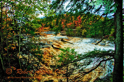 Blazing autumn foliage frames roaring Presque Isle River's Manido Falls within Porcupine Mountains Wilderness State Park (USA MI Ontonagon)