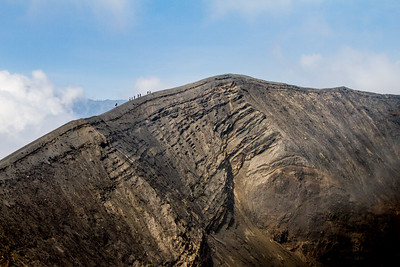 People carefully cross the narrow rim of Mount Bromo.