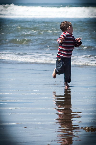 Boy running from waves
