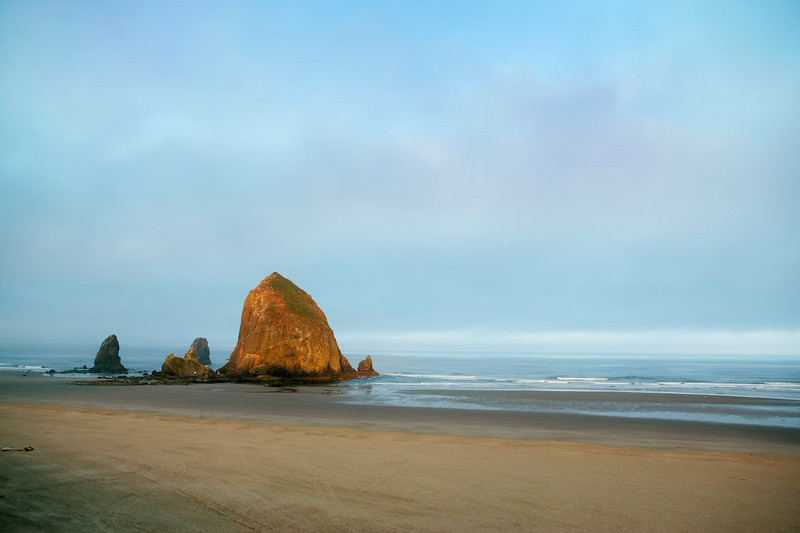 First light just hitting Haystack Rock at Cannon Beach, Oregon. This is a nine-mile wide sandy beach, that features Haystack Rock, the third largest coastal monolith in the world, at 235 feet high. Haystack Rock has been designated as a marine and bird sanctuary. The tidepools around the rock have many intertidal animals in them, including limpets, barnacles, starfish, crabs, sea sculpins and anemones. Several bird species nest on the rock in the summer. The most colorful of these is the Tufted Puffin.
