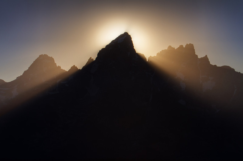 Rays and shafts of light dance behind the peak of the Grand Teton mountain as the sun begins to set directly behind it.