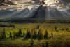 Sunburst through clouds at sunset over Grand Teton mountain range, Grand Teton National Park