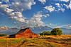 Morning clouds begin to clear as the sunlight hits the Moulton Barn in Grand Teton National Park.