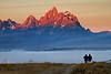 Morning mist hangs ove Snake River valley in National Park as sunrise light hits Grand Teton peak.