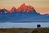Morning mist hangs ove Snake River valley in National Park as sunrise light hits Grand Teton peak.