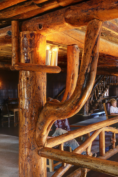 """This large corner support with its two bracing limbs are some of interior lodgepole pine construction details in this series.  Old Faithful Inn is a spectacular log (lodgepole pine) hotel that was initially built in the wunter of 1903-1904. It is the largest log hotel in the world and possibly even the largest log building in the world. There have been several additions made over the years to this building, but this lobby is original to 1903-1904. It remains a prime example of the """"Golden Age"""" of rustic resort architecture (Robert Reamer was the architect)."""