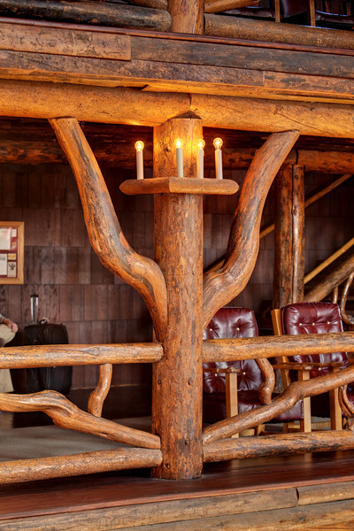 """Interior details of lodgepole pine construction. Old Faithful Inn is a spectacular log hotel in Yellowstone National Park that was initially built in the winter of 1903-1904. Construction of the inn was mainly using locally-obtained materials including lodgepole pine (the bark was later removed in 1940). When it first opened in the Spring of 1904, it boasted electric lights and steam heat. Old Faithful Inn is the largest log hotel in the world and possibly even the largest log building in the world. There have been several additions made over the years to this building, but this lobby is original to 1903-1904. It remains a prime example of the """"Golden Age"""" of rustic resort architecture (Robert Reamer was the architect)."""