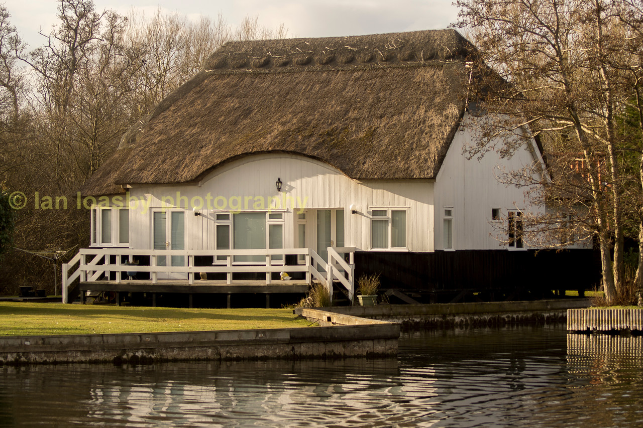 Riverside thatched white cottage