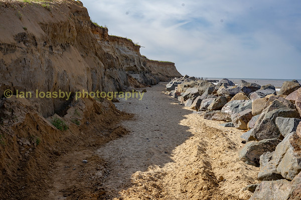 In this view of the bottenm of the cliffs you can see just how unstable they are hence the wall of boulders in place in front of them to slow down the effect of storms breaking against them
