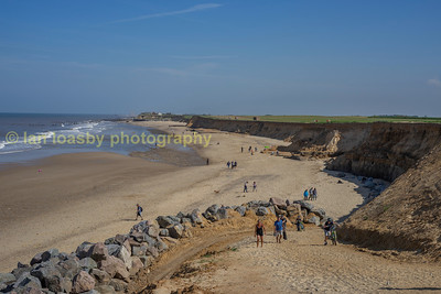 Happisburgh is probably better known for the local coastal erosion, in the foreground can be see the new sea defences of large boulders piled up to about a height of 4 ft and stand proud of the bottom of the cliff face dissipating the power of the incoming sea, this view looking south shows the new ramp built by the contractors contracted to carry out the sea defence work which allows access to the beach
