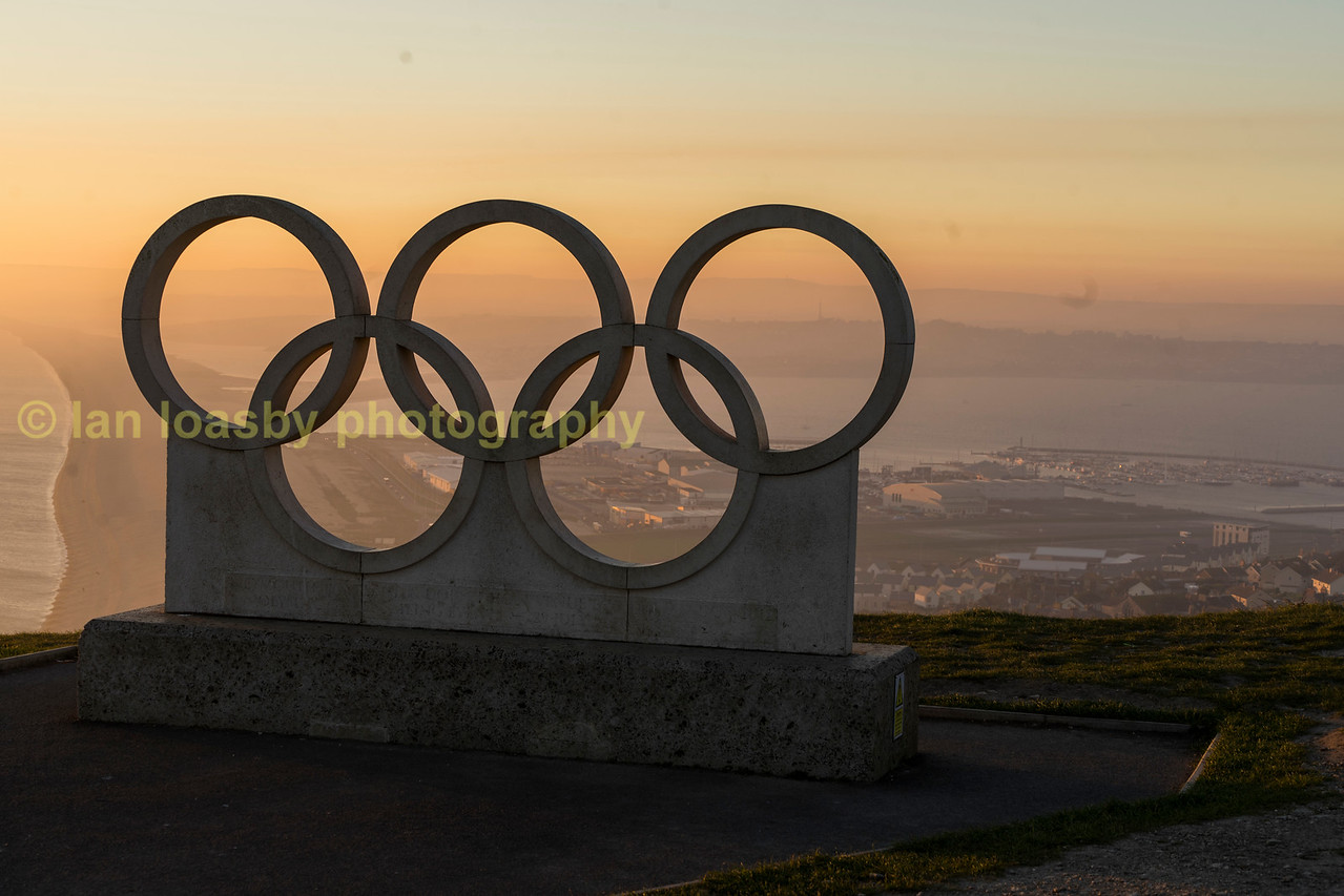 The Olympic rings tower over Chisel beach & Weymouth  from a veiwing point on  Yeates Rd,  Fortunewell, Portland, to celebrate Weymouth hosting the London 2012 Olympic sailing events