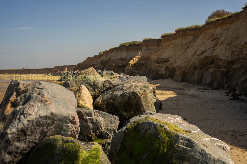 The boulder sea defences and sandstone cliff at Happisburgh