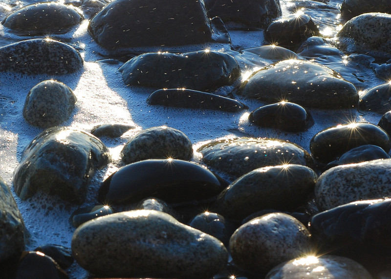 Beach cobbles with a glint of late afternoon sun