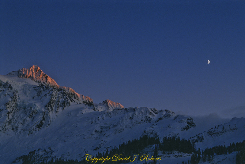 A winter sunset view of Mount Shuksan and the moon from the Mount Baker Ski Area