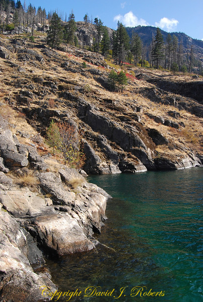 Rocky shoreline of Lake Chelan with azure blue waters