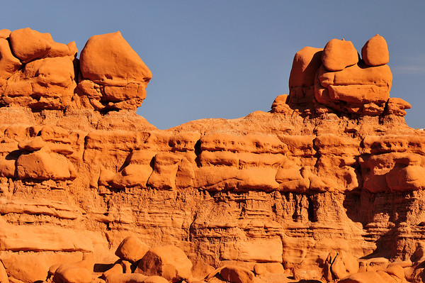 """Goblin Valley State Park, UT. """"Froggy"""" a sculpted rock formation is perched above, watching over the amphitheater. <br /> From deposits laid approx. 170 million years ago, Goblin Valley State Park has been sculpted by forces of nature by the forces of wind and water.  The goblins are made of Entrada sandstone which shows evidence of being near an ancient sea millions of years ago. The edges of the sandstone weather more quickly producing spherical-shaped goblins."""
