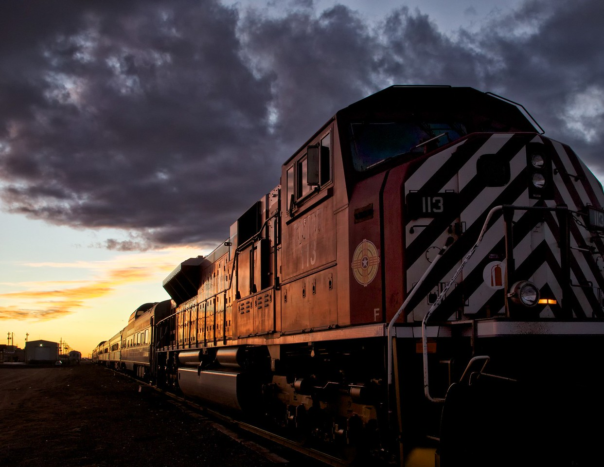 Last West Texas sunset of 2012. This is a passenger train and some very old cars are visible.