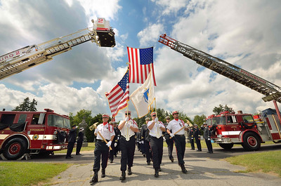 The Fitchburg FD Honor Guard passes under the American flag draped from Tower Ladder 2 and Barre Ladder 1 (old Fitchburg Ladder 3)