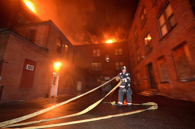 "Lt Tony Lefebvre stretches a 2 1/2"" in the rear of the building at the Leominster 7th Alm in November."
