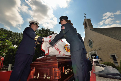 D.C. Dave Rousseau and FF Kristy Pappas drape the casket of FF Jim Roy with the department union flag as Engine 4 prepares to depart the church.