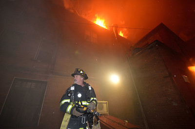 "Leominster FF Bill Bisol stretches a 2 1/2"" into the rear alley at the 7th Alm in November."