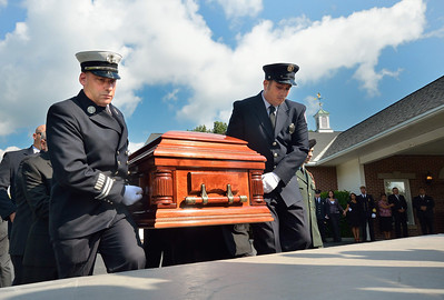Pall bearers Capt Tad Dateo and FF Andrew Roy load the casket of FF Jim Roy onto Engine 4.