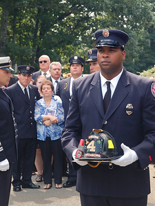 FF Rob Dacosta bears Jim Roy's helmet and his family looks on as his casket is placed on Engine 4 for the last time.