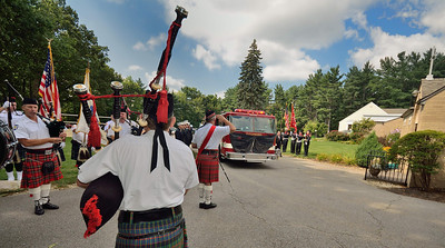 Drum Major, Chief Fred Leblanc (Leominster FD retired) salutes as Engine 4 arrives at Our Lady of the Lake church, while the massed band plays.