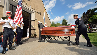 FF Patrick Haverty looks away as the casket of FF Jim Roy is wheeled into the church.