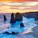 """""""12 Apostles at Sunset"""" Great Ocean Road, Victoria, Australia. The 12 Apostles has been at the top of my bucket list ever since seeing images of this amazing place! I had a business trip to Australia this summer and managed to head down the Great Ocean road (on the other side of the road!!) to capture this. I went during mid-day to scout and came back for fantastic sunset. I just 'found' my images again and finally published this one. I hope you enjoy it and add it to your list of amazing places to go! You can see the location via Google Maps here: <a href=""""http://g.co/maps/g4w9d"""">http://g.co/maps/g4w9d</a>     This image looks great above the couch or in a conference room. A recent collector did this as a 24"""" x 36"""" HD Acrylic Crystal Flex image just glowing on the wall.  Fine Art Images for Collectors, Healthcare and Corporations. Perfect for Executive Briefing Centers."""