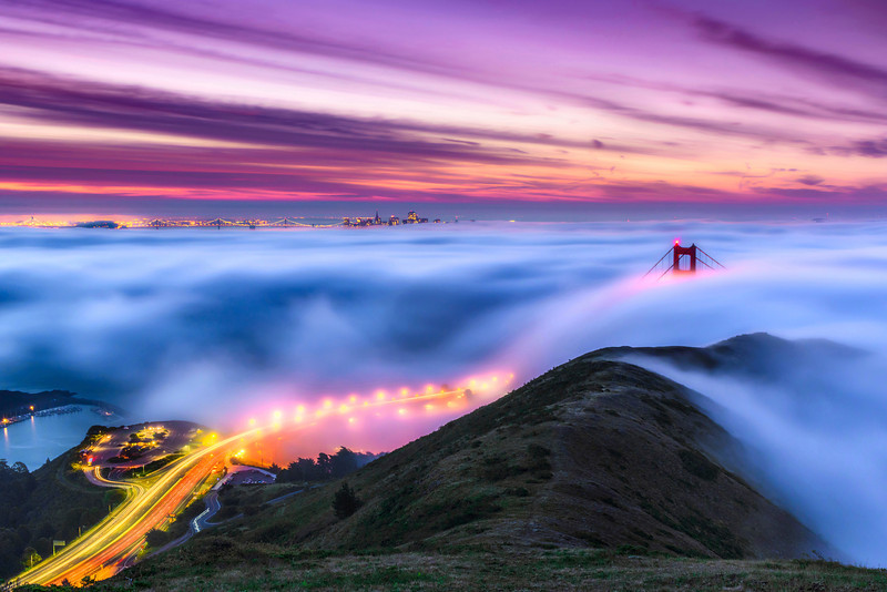 "A portion of ""Above the Fog""  The original panorama can be seen here: <a href=""http://bit.ly/1bmDXFx"">http://bit.ly/1bmDXFx</a>  I love shots of San Francisco and the Golden Gate Bridge but never had gotten the perfect shot with the Golden Gate Bridge poking through the fog. I saw the weather report at 11:30pm the evening before saying ""your commute will be slow in the morning with low lying fog across the Golden Gate Bridge"" I thought PERFECT! I'll head up in a few hours! I set out in the dark for the drive up to San Francisco to shoot from the Marin Headlands.<br /> <br /> The hike up the hill in the dark and the fog with too much camera gear (30 pounds!) gave me a great early morning workout! I arrived just as the sky was starting to have an amazing glow and the fog was swirling beneath the bridge. I decided to go for a longer exposure to capture the lights of the cars heading to the Golden Gate Bridge. On the right side of the photo you can see some cars heading along Conzelman Road. I just love the curves and swirling fog together with the bumps in the hillside. It only took me a month to process my image :-)<br /> <br /> The glow of the San Francisco lights, Car lights and Golden Gate Bridge and colors in the sky balanced with the greens of the hill and fog are what caught my eye. I went for a 1:2 panorama format for this which will look great above a fireplace, couch or in an executive boardroom printed 30"" x 60"" or larger!<br /> <br /> This a single shot from the Nikon D800, Nikon 28-70mm f/2.8 lens (28mm), 30 seconds, f/13 and ISO 200. This is processed in Lightroom 4 and post processing in Adobe Photoshop CS6. I did not bring my Singh-ray neutral density filters on this trip but used the awesome digital ND filters in LR4 - my favorite feature of LR4!<br /> <br /> It is always a crap shoot as it can be clear in the Southbay down in Sunnyvale where I live and how the fog is in San Francisco. Sometimes the fog is higher up and obscures everything and never clears! That is part of the joy, frustration and chase of great photographs - the weather and lighting will NEVER be the same!!! (but meeting cool people when you are out is another great benefit!)<br /> <br /> I'll be showing this print at my open house coming up May 11th and 12th in Sunnyvale. Contact me for more information!! Copyright John Harrison Photography <a href=""http://www.jharrisonphoto.com"">http://www.jharrisonphoto.com</a><br /> <br /> Here is a fantastic quote from one of my followers that I really love! ""••••• John you took the picture with your magic mind and hand and you made San Francisco the place where the angels live.........."