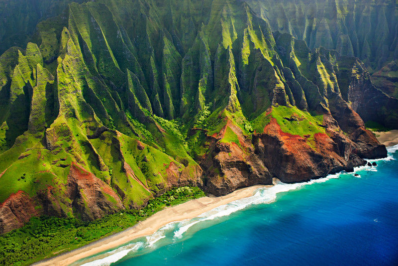 """""""Late afternoon along the Na Pali Coast in Kauai"""". I chartered a Helicopter in Kauai in hopes of getting THIS shot! 6 schedules due to changing weather and 3 passes along the Na Pali Coast and I got the shot I was looking for! Some amazing colors like the deep blue in the water, the green and red cliffs and the incredible folds along the cliffs! Just flying back and forth for a few hours over Kauai with the doors off in an R-22 (small) helicopter! Aerial Photograph of the Na' Pali Coast captured from a Helicopter in Kauai. Aerial Photography in Kauai is fantastic!   Fine Art Photography for Collectors, Healthcare and Corporations. Perfect for Executive Briefing Centers."""