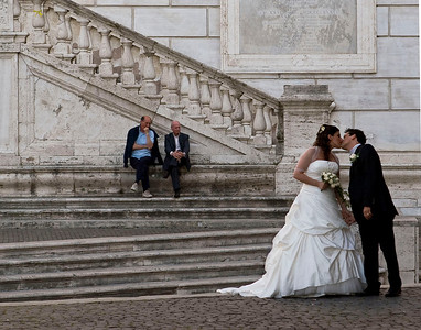 A newly married couple kisses in the piazza.