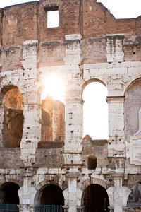 The sun shines through one of the arches in Colosseo, the Roman Colosseum, near sunset.