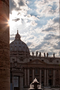Saint Peter's Basilica in the high contrast afternoon sun viewed from behind a column in Vatican Square.