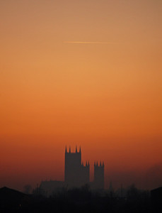 High on the hill in the distance Lincoln Cathedral stands dark against the sunset afterglow, as a lone aircraft flies high overhead