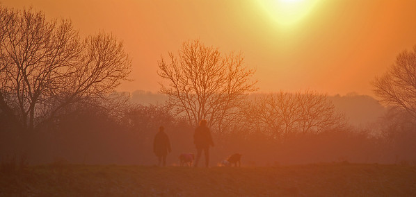 Dog walkers on the riverbank at sunset. Despite the golden light it was very cold. You can see the dog's breath.