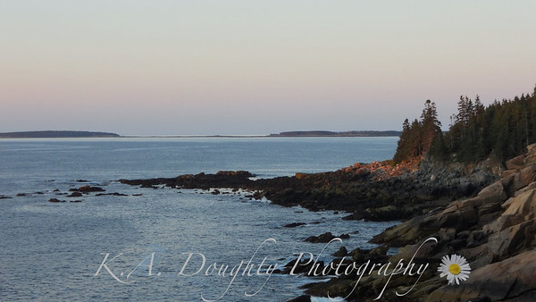The rising sun begins to color the rocky shore
