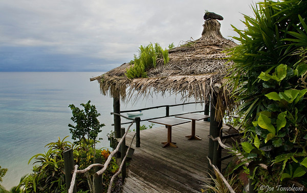 A tiki hut overlooking the calm South Pacific as a thunderstorm looms on the horizon.  Taveuni Island, Fiji