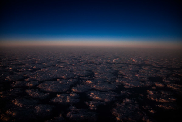 High altitude aerial view of cloud tops at sunset with a black sky