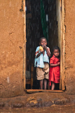 Two children in rural Masaka taking shelter from a rainy season downpour.  Many of these houses are made from a mud and cow dung mix.  The lucky ones have metal sheeting on their roofs.